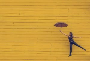 Women jumping with umbrella on a yellow background