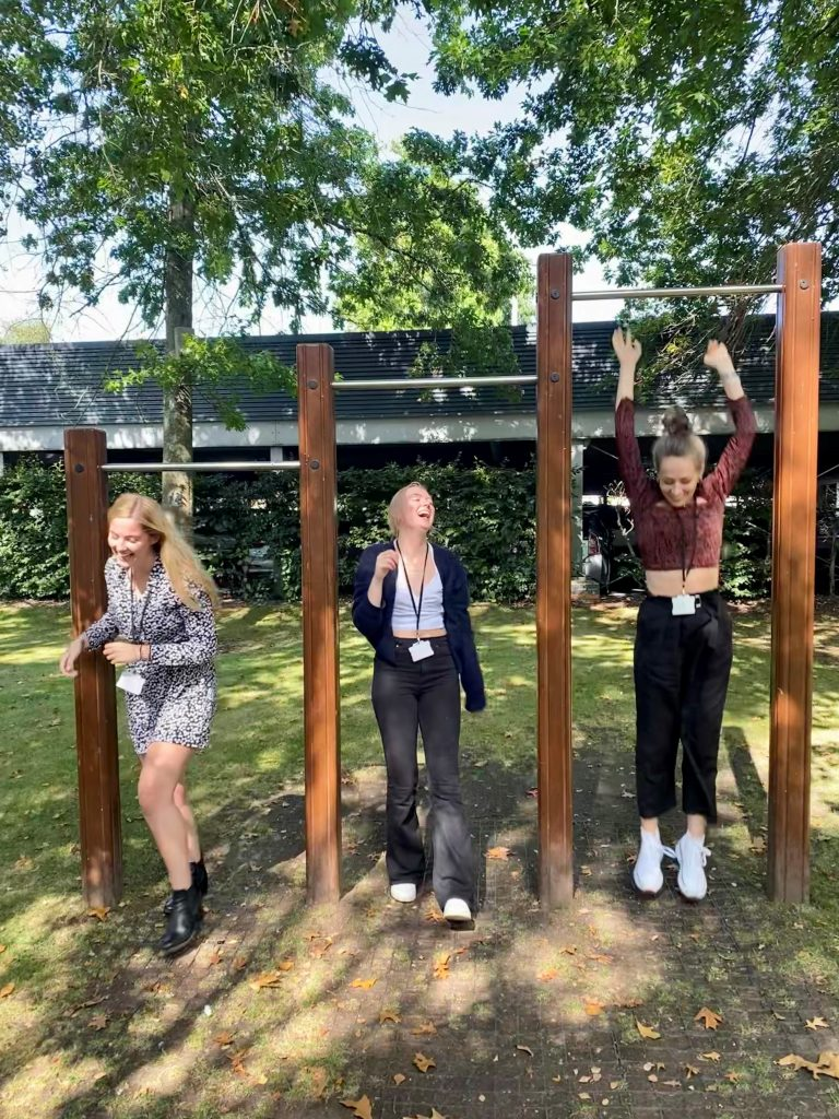 Jess, Polly and Lucy jumping down from outdoor pull up bars.